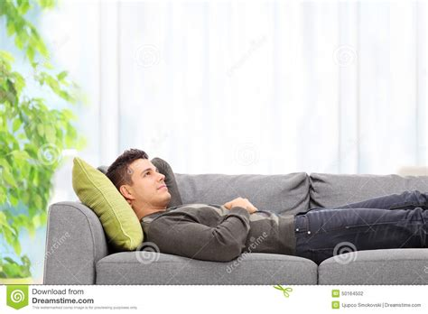 lying on sofa young man lying on a sofa at home stock photo image