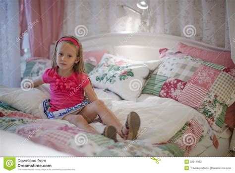 big girl bed little girl sitting in a big colorful bed stock