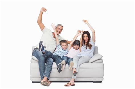 family sitting  sofa raising  arms stock photo