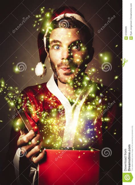 the magical christmas creative 1539967875 gift wrapping santa with magical christmas present stock photo image 61589926