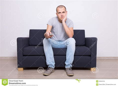 man on sofa bored man sitting on sofa and watching tv at home stock