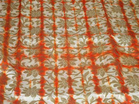 Sarung Tenun Motif Ahd Orange silk brocade fabric in beige orange and gold motifs pattern