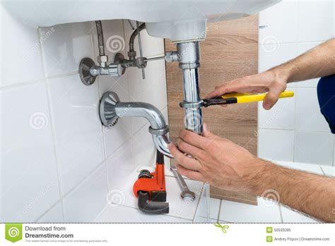 bathroom fixing male plumber lying on floor repairing sink in bathroom
