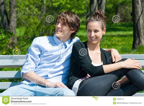 couple sitting on bench couple sitting together on park bench stock photos image 19500713