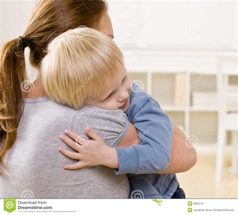 mother comforting child mother hugging and comforting her son stock photography