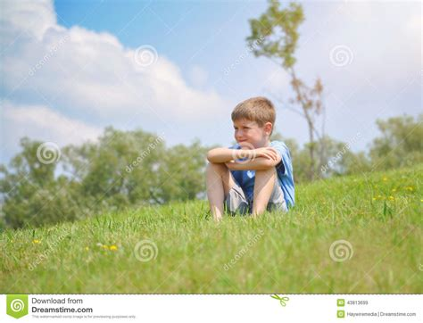 boy on boy boy sitting on green nature hill outside stock photo