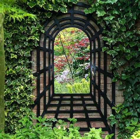 A Mirror Trompe L Oeil Creates A Focal Point On A Garden Garden Wall Mirrors