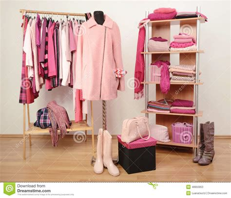 dressing closet with pink clothes arranged on hangers and