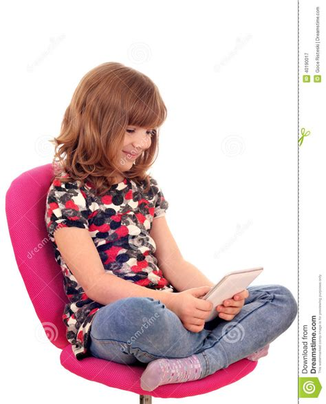 little girl on chair little girl sitting on chair and play with tablet pc stock
