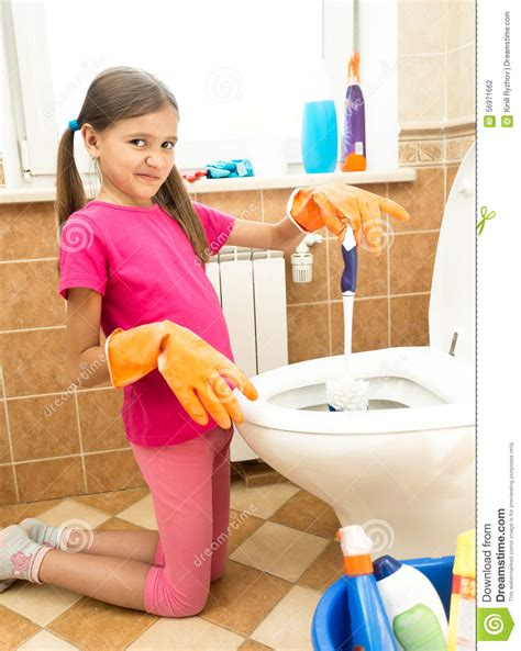 a girl using the bathroom portrait of girl cleaning toilet with disgust stock photo