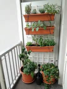 a vegetable garden on a small balcony hanging planters with herbs red peppers and
