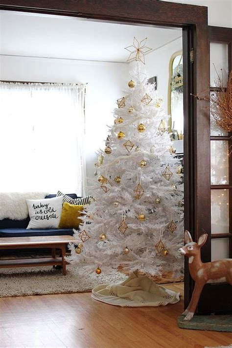decorating a white christmas tree with beautiful gold