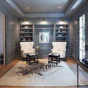 den design black paneled den with built in shelves and brass picture