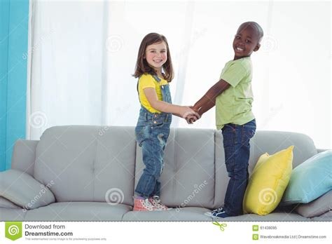 standing on the couch happy boy and girl standing up stock photo image 61438095