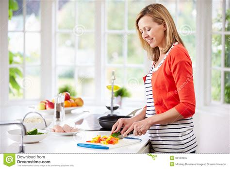 Kitchen Lights Over Table Woman Standing At Counter Preparing Meal In Kitchen