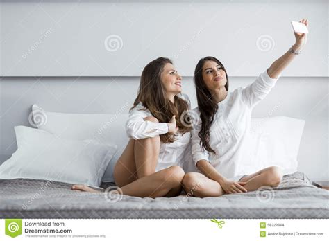 two girls in bed two hot girls lying on a bed taking a photo of themselves