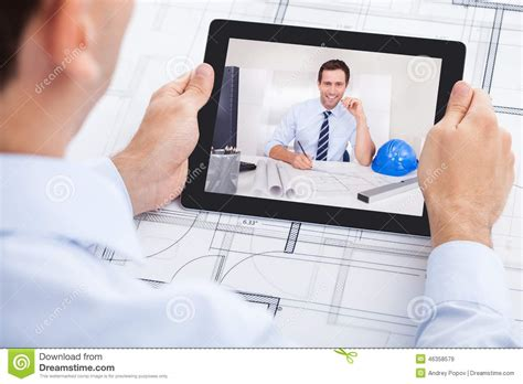 male architect with digital tablet studying plans in architect video conferencing with colleague stock photo