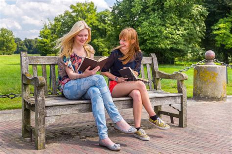 girls bench girls sitting on wooden bench in park reading books stock