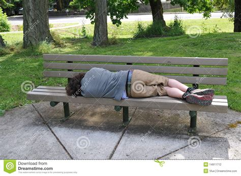 on bench sleeping on a bench in a public stock photo image of