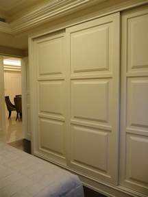 sliding closet door bedroom with armchair bed skirt