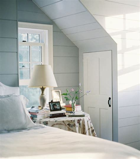 unique slanted ceiling with white bed and pastel grey