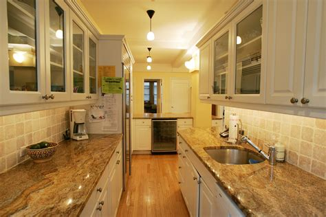 brown granite countertop connected by white wooden kitchen