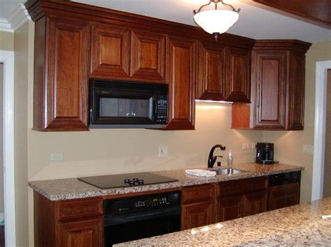 cherry cabinets black appliances the warm tones of these