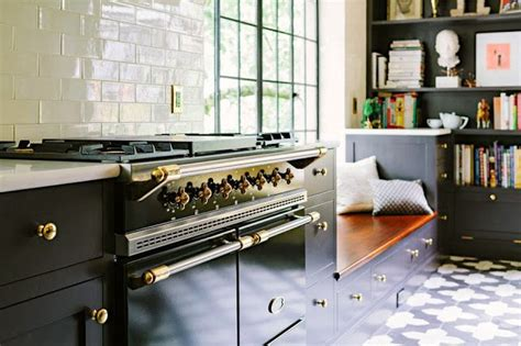 white kitchen cabinets with brass hardware and black lacanache range stove in black with gold brass knobs