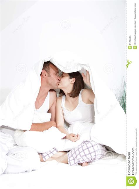 romantic couple in bed images couple kissing under the bedclothes royalty free stock