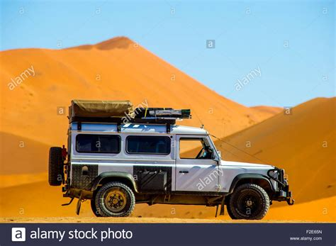 land rover desert land rover defender 110 parked in the desert with dunes in