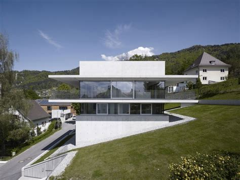 partially cut into the hillside house by the lake in