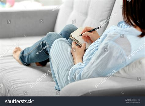 pregnancy couch pregnant woman writing notebook sitting on stock photo