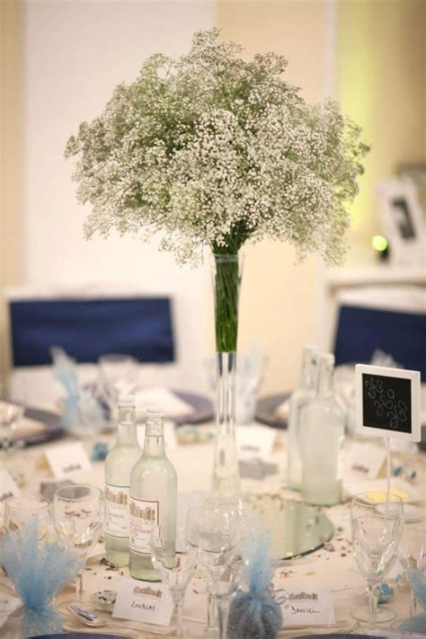 slim vases filled with gypsophila on the tables