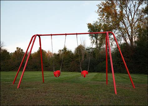 red swing set a red swing set in the warm light of sunset photograph
