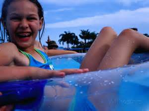 Young girl floating in swimming pool in rubber ring gold coast