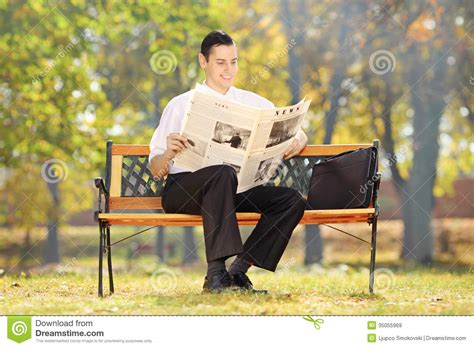 seated bench businessman seated on a bench reading a newspaper in a
