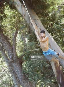 swinging on rope young man swinging on rope by trees laughing stock photo