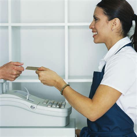 cashier handing credit card to customer perfecting community development corporation