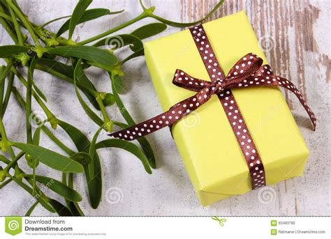 yellow soft christmas gift wrapped yellow gift for and mistletoe on wooden background stock photo image