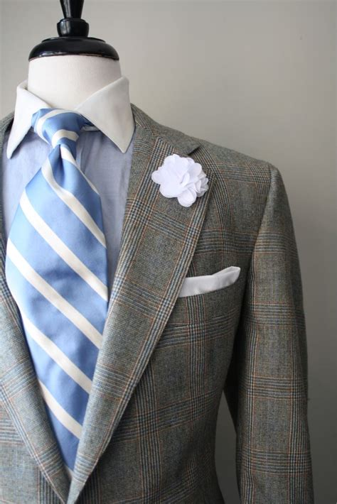 striped tie and checkered shirt beneath an elegant grey light grey suit with blue and orange plaid light blue