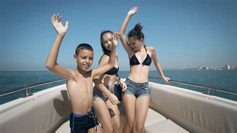 girl dancing on boat with kid girl kissing a boy little boy and girl sitting on a pier