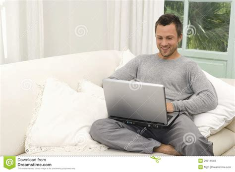 man on sofa man on couch with laptop at home royalty free stock
