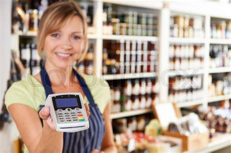 sales assistant in food store handing credit card machine to customer stock photo colourbox