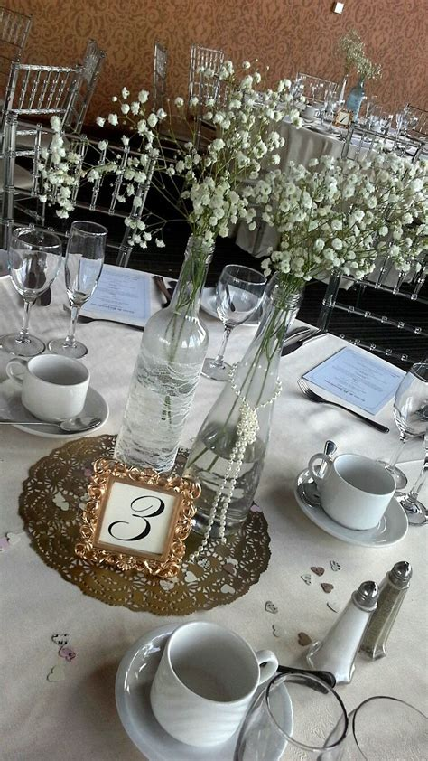 wine bottles, babies breath and pearl centerpieces for a