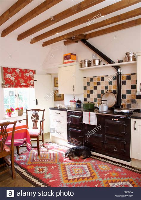 Traditional Rug Uk by Beamed Country Kitchen With Small Dog Lying On Red