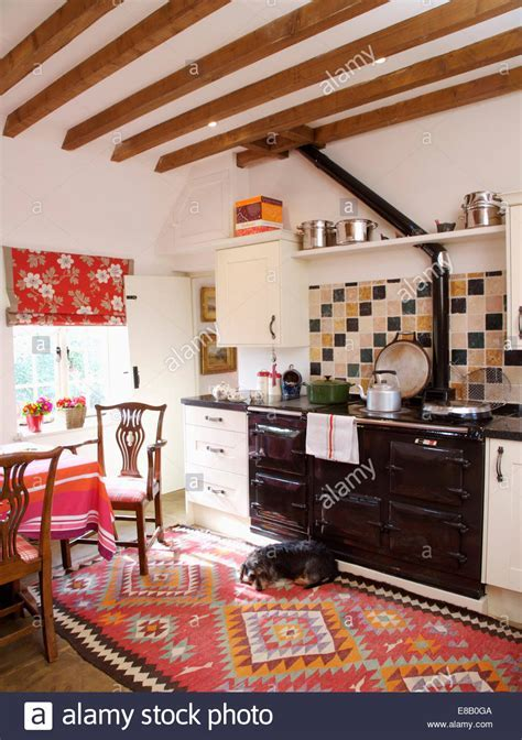 Beamed country kitchen with small dog lying on red