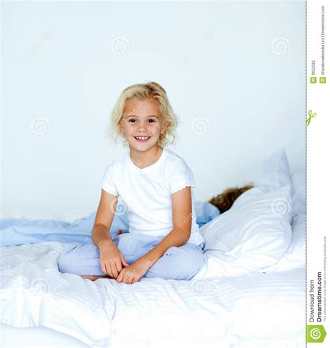 girl sitting on bed smiling blonde girl sitting on a bed stock photography