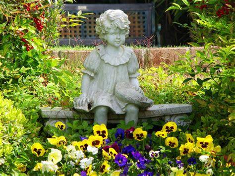 little girl sitting on bench statue my garden queen bee