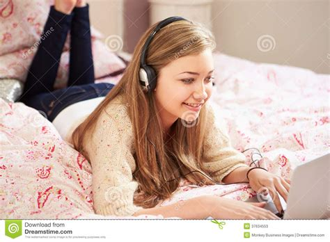 girl on bed teenage girl lying on bed using laptop wearing headphones