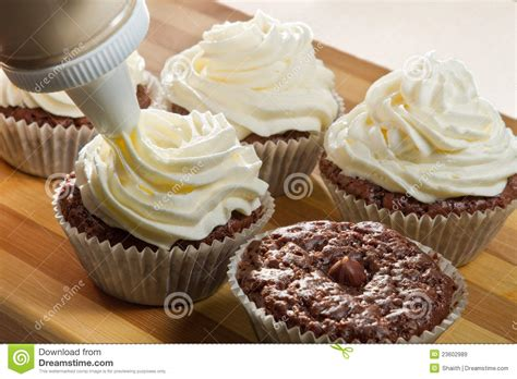 decorating chocolate muffin with vanilla cream royalty free stock images image 23602989